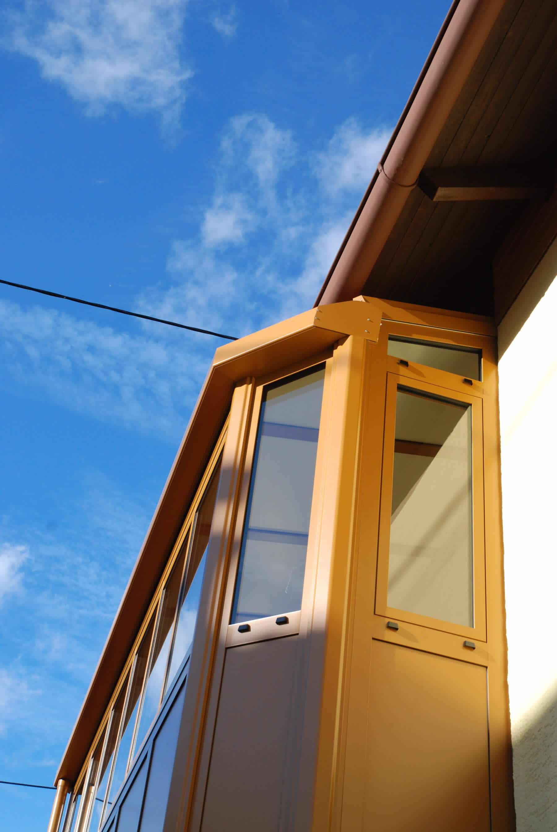 Balkonverbau mit geschlossenem Dach und Faltschiebefenster in ockerbraun