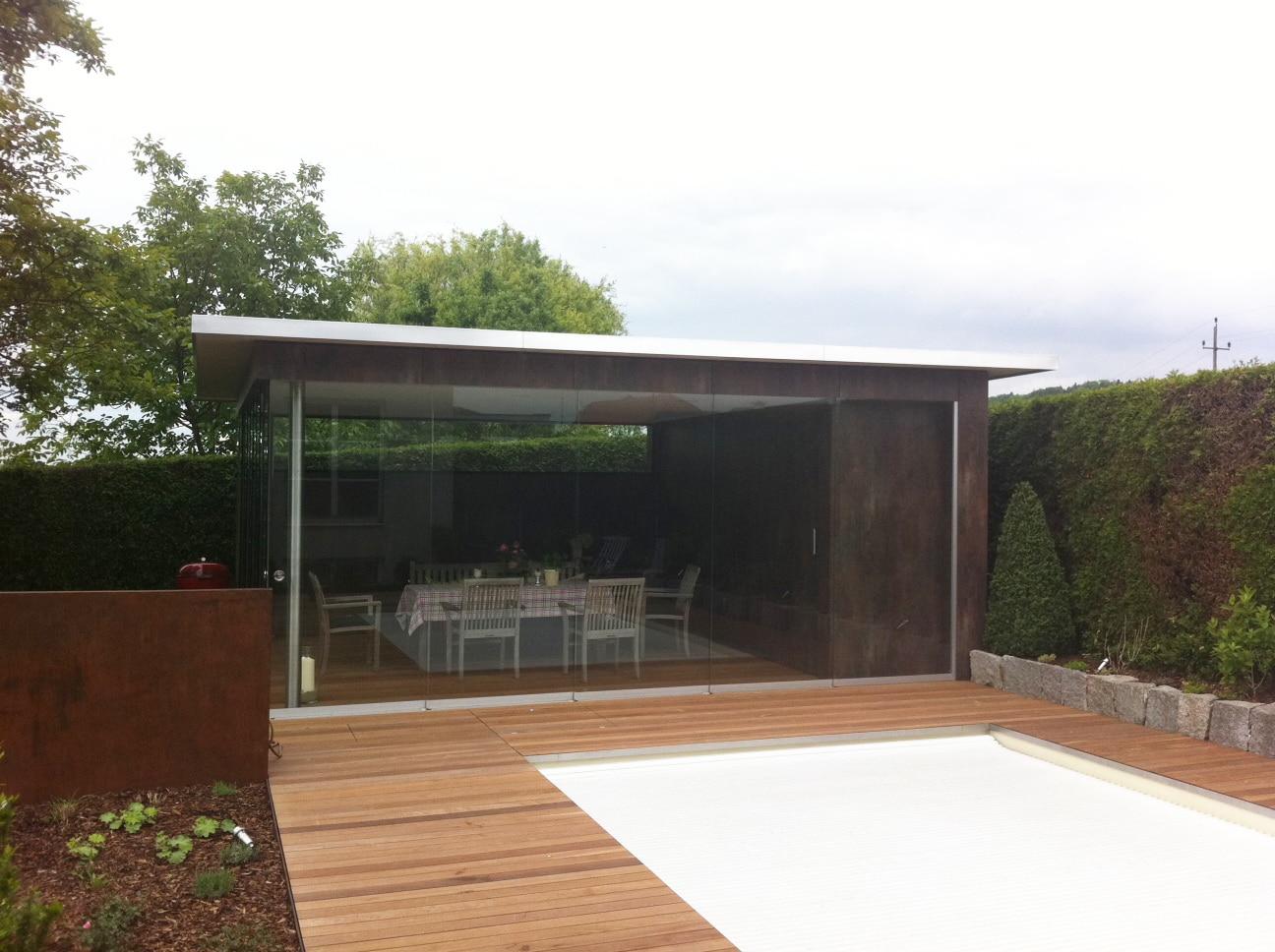 Freistehendes Gartenhaus am Pool mit Glasschiebeelementen