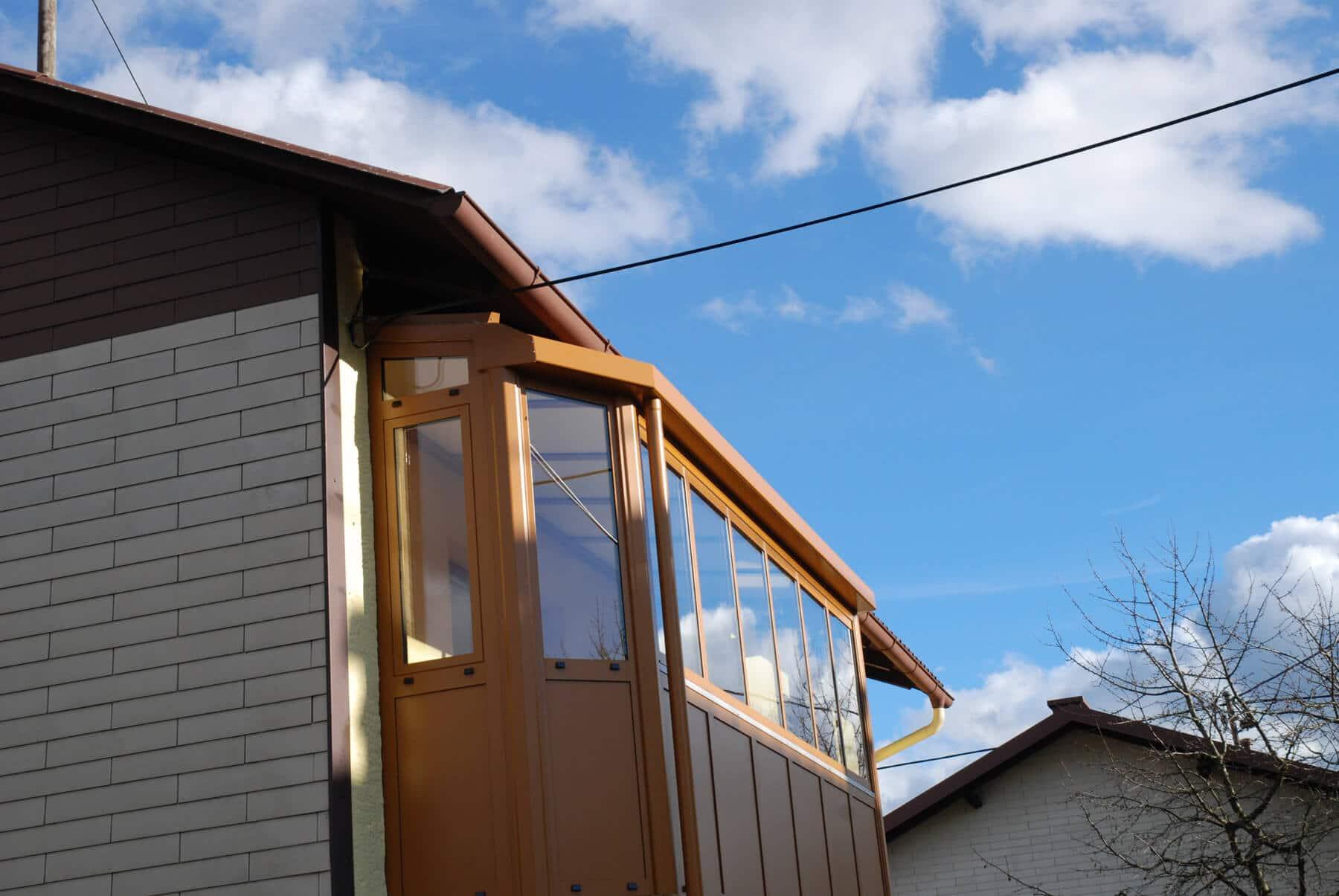 Ockerbrauner Balkonverbau mit öffenbaren Faltfenstern