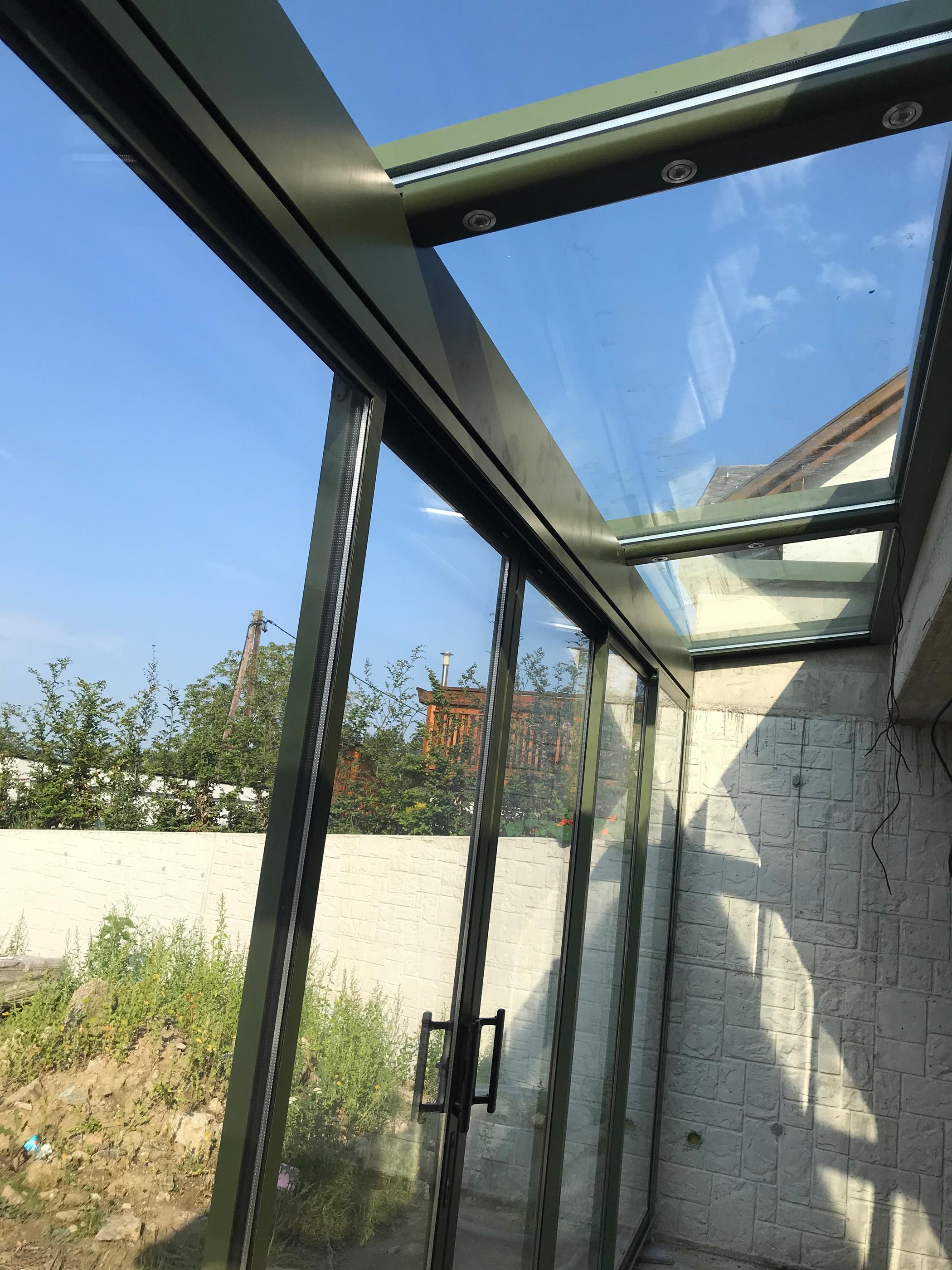 Wintergarten mit kleinem Glasdach und Schiebefront
